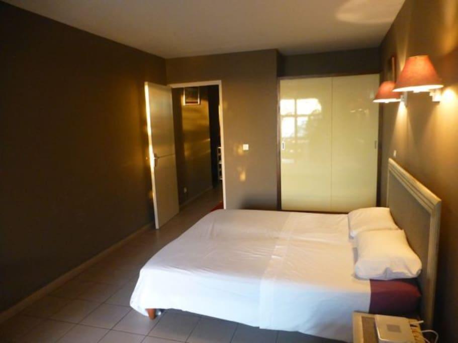 Une chambre qui donne sur la terrasse et qui est séparée de la kitchenette par une porte