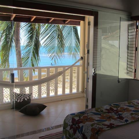 Quarto com ar condicionado, varanda e vista mar e praia.