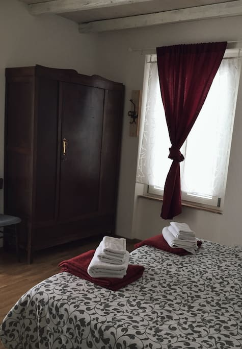 Private bedroom with ancient wood wardrobe and window with mountains view. Towels included