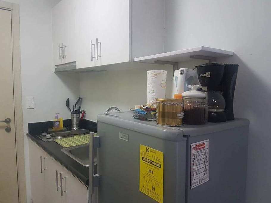 A Kitchennette with a refrigerator and stove and kitchen utensils.  A microwave will also be available with tea pot and coffee machine for brewing and a selection of complimentary organic beverages (coffee,  tea and juices)