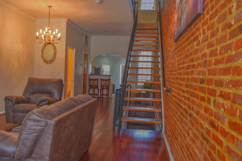 Rowhome with hardwood floors & exposed brick wall