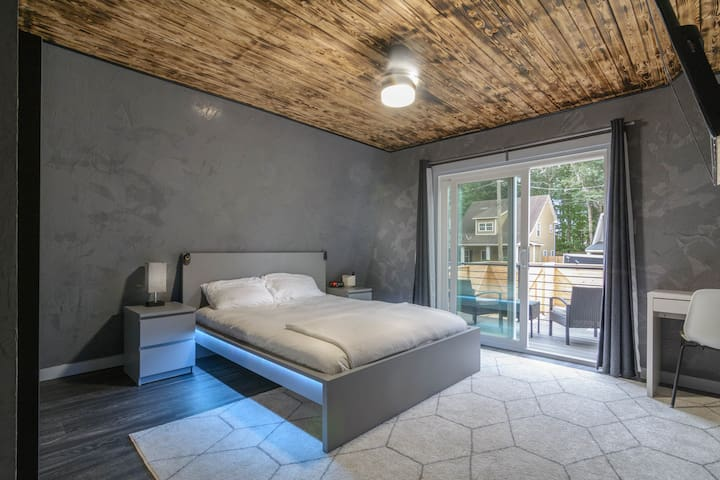 The first bedroom features a queen size bed and a balcony looking over the back yard.