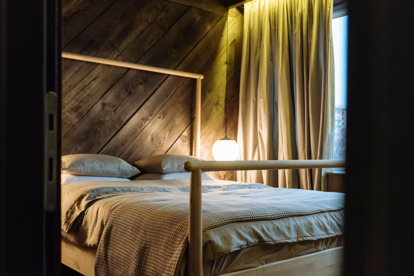 The wooden panels behind the bed give the room real warmth