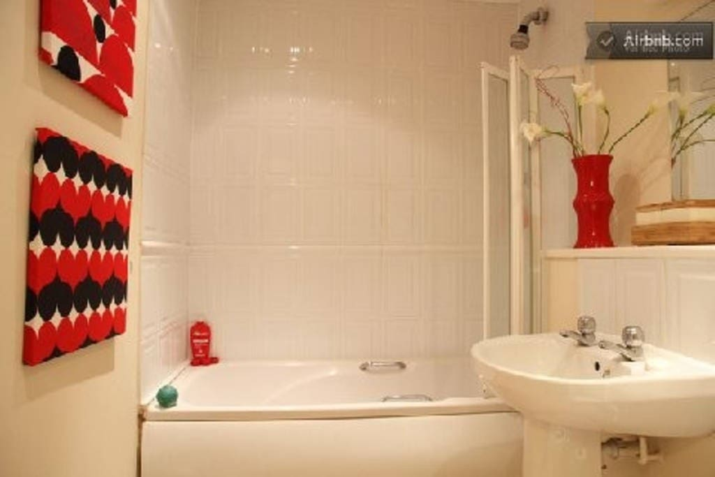 Bathroom with power shower and bath.