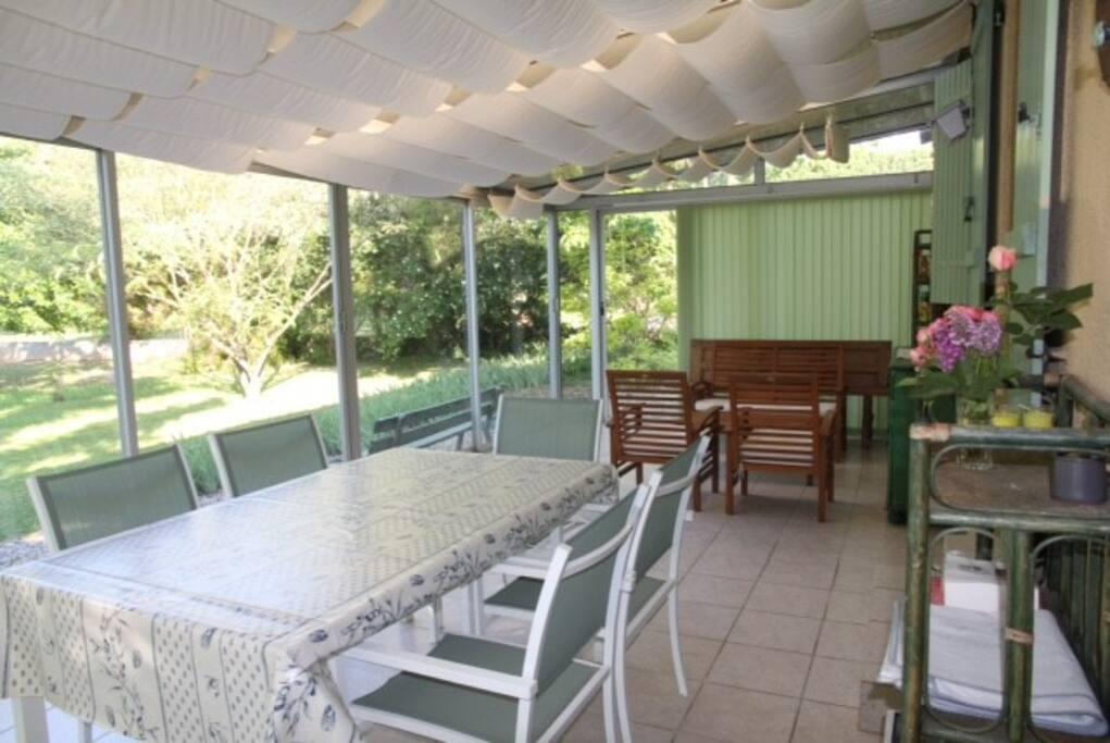 Une véranda sur le jardin de 32 m² avec salon et table pour le repas