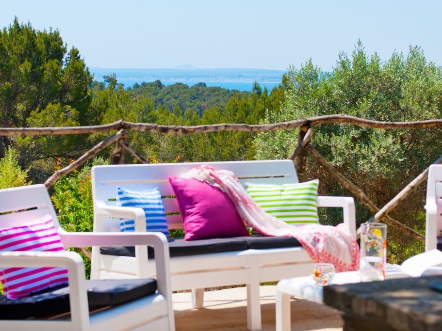 """Zona de Sofa exterior """"Blanco"""" con sombra natural y vistas a la Bahía de Alcudia"""