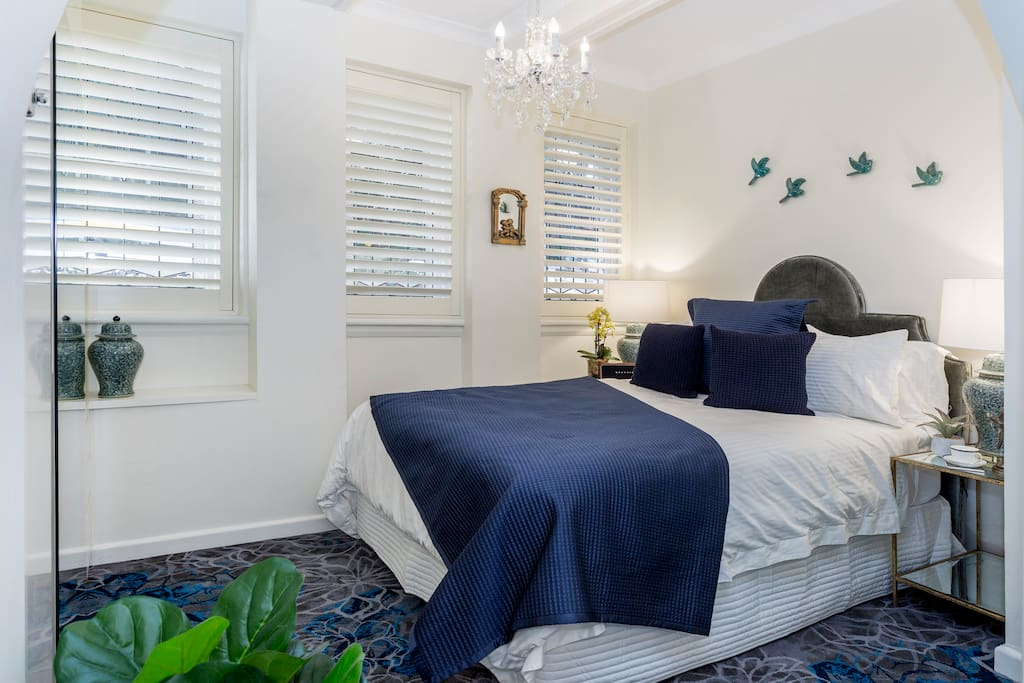 The bedroom features a Queen Bed with Luxury Bedding, with bi-fold doors to close off from the living area.