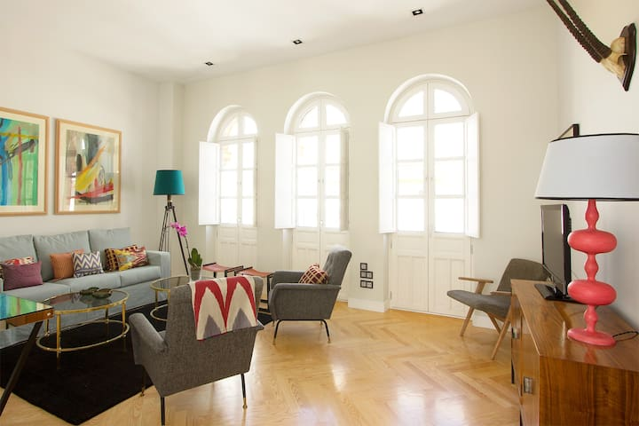 Living room with 3 windows. Furnishes include a sofa and 2 armchairs.