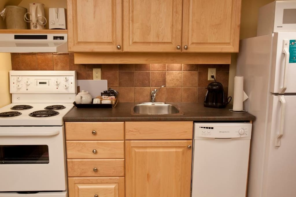 Functional Kitchen with Oven, Stove, Dishwasher, Fridge, Toaster and coffee maker.