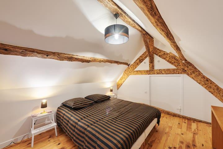 Chambre alcôve semi fermée avec salle de bain attenante et petit salon avec canapé lit 2 places