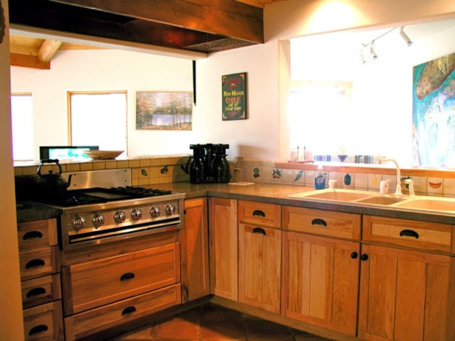 Upgrade stainless cook top range overlooks living room with mountain views