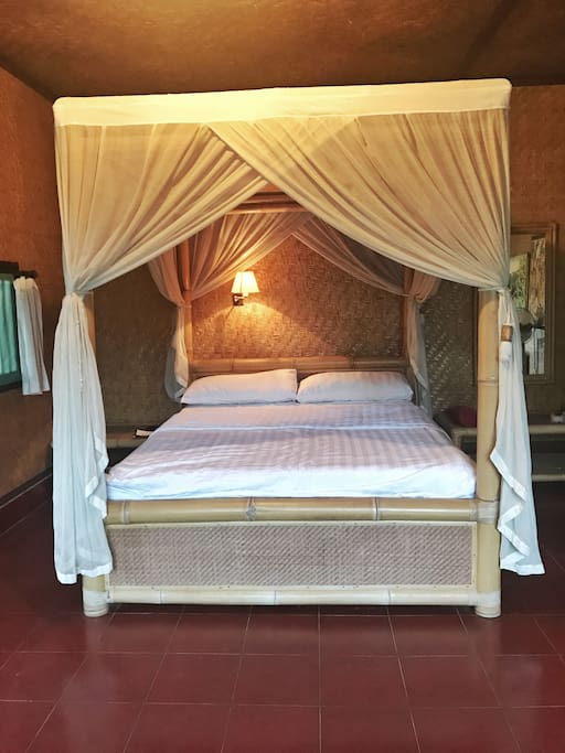 Double bed which has a mosquito net and reading lamp.