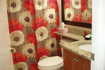 Private bathroom with tub, and shower, granite countertop.