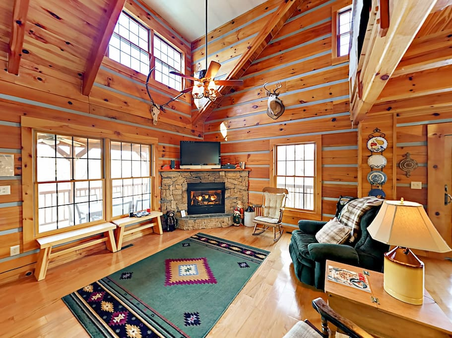 Open-concept living area with soaring ceilings, exposed beams, and warm wood paneling.