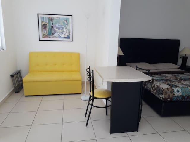 Área de descanso, en la que se ubican sillón, lámpara de piso, cuadro decorativo y un tendedero de ropa retráctil.