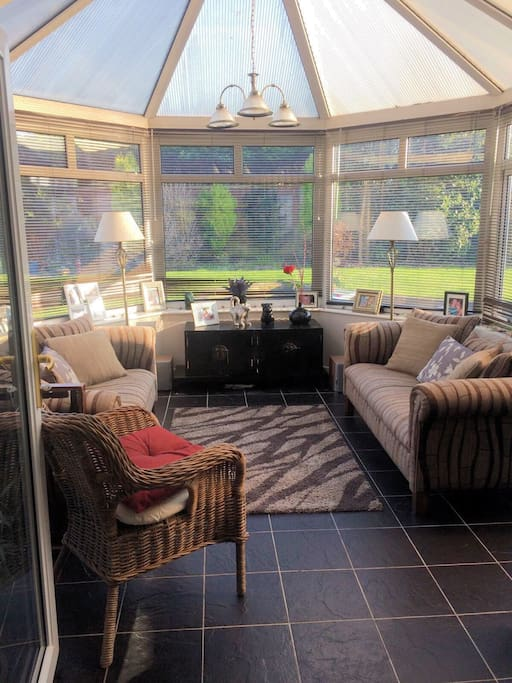 Conservatory lounge for relaxing. Overlooking the garden, this beautiful sitting/dining room has the benefit of a TV and music centre.