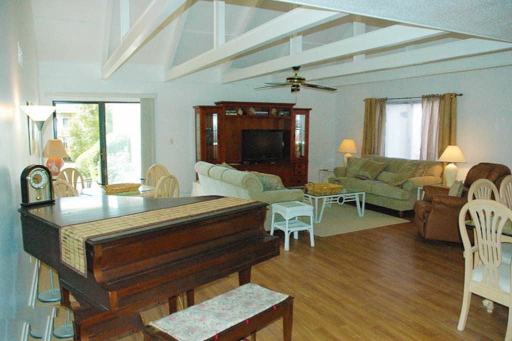 Large living area with vaulted ceiling, flat screen TV and access to the patio.