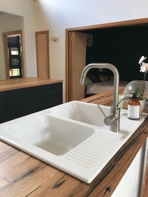 Gentle recycled timber countertops and large ceramic farmhouse sink make the kitchen a joy to use.
