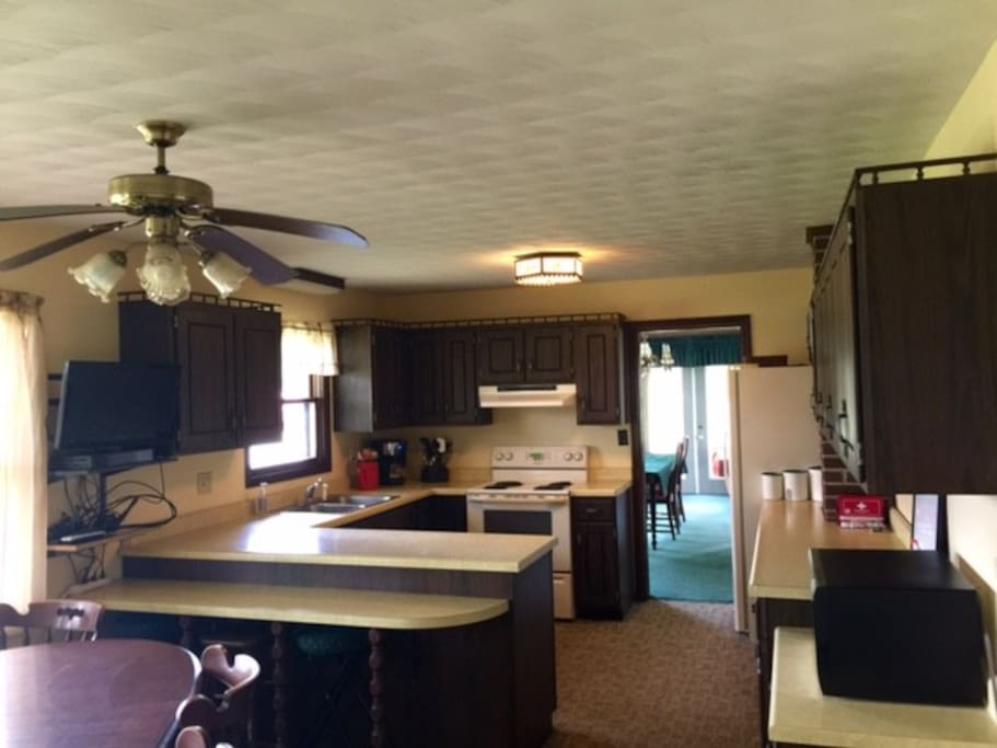 kitchen includes stove, microwave, coffee pot, dishwasher, and tv