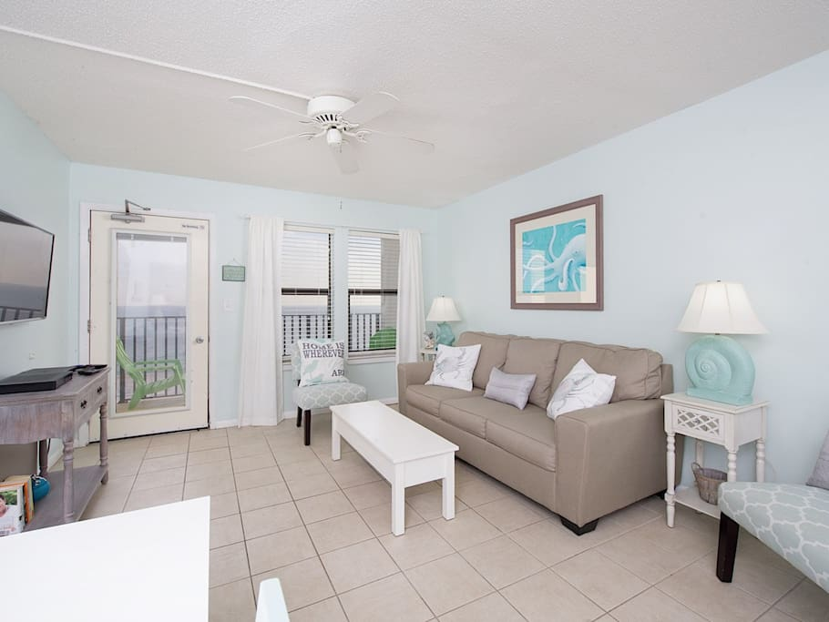 The sunlit living room features tile floors, stylish furniture, and a beach-inspired color palette.