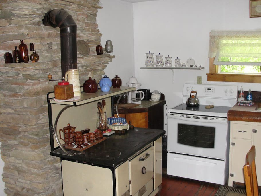 "The country kitchen includes a ""modern"" electric stove along with Grandma's classic cook stove."