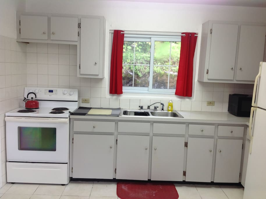 Bright, light and fully equipped kitchen - stove, fridge, microwave, coffeemaker, washer, dryer, and table and chairs.