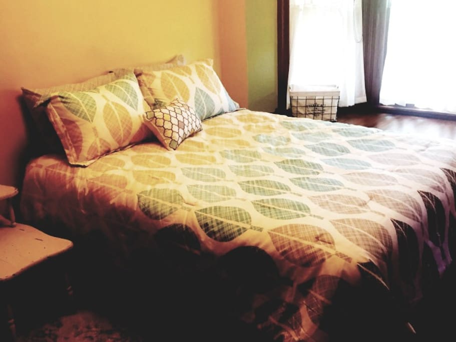 Queen bed in room with bay window and quaint window seat. This room also has a small workspace desk.