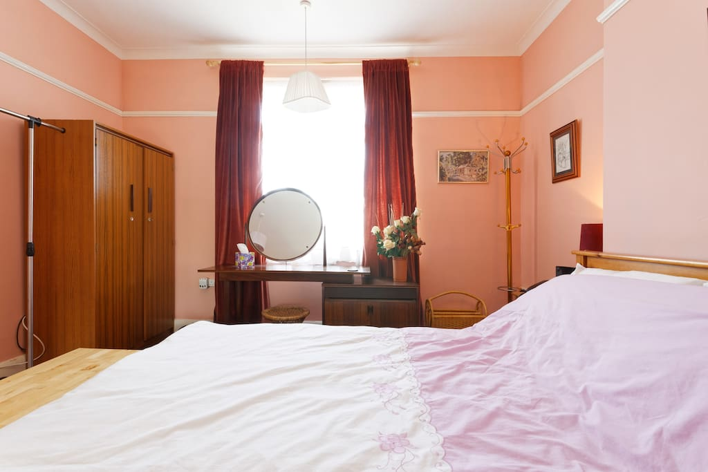 Comfortable and cosy bedroom available for reservations:  Bedroom overlooks the garden and has plenty of storage and hanging space - 2 wardrobes with hangers, dressing table, clothes rail, trunk, coat stand, bedside drawers, and chest of drawers. All the amenities for a couple, 2 friends or an individual to feel at home and relaxed.