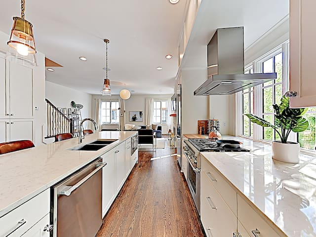 Granite countertops and stainless steel appliances sparkle in the brand-new kitchen.
