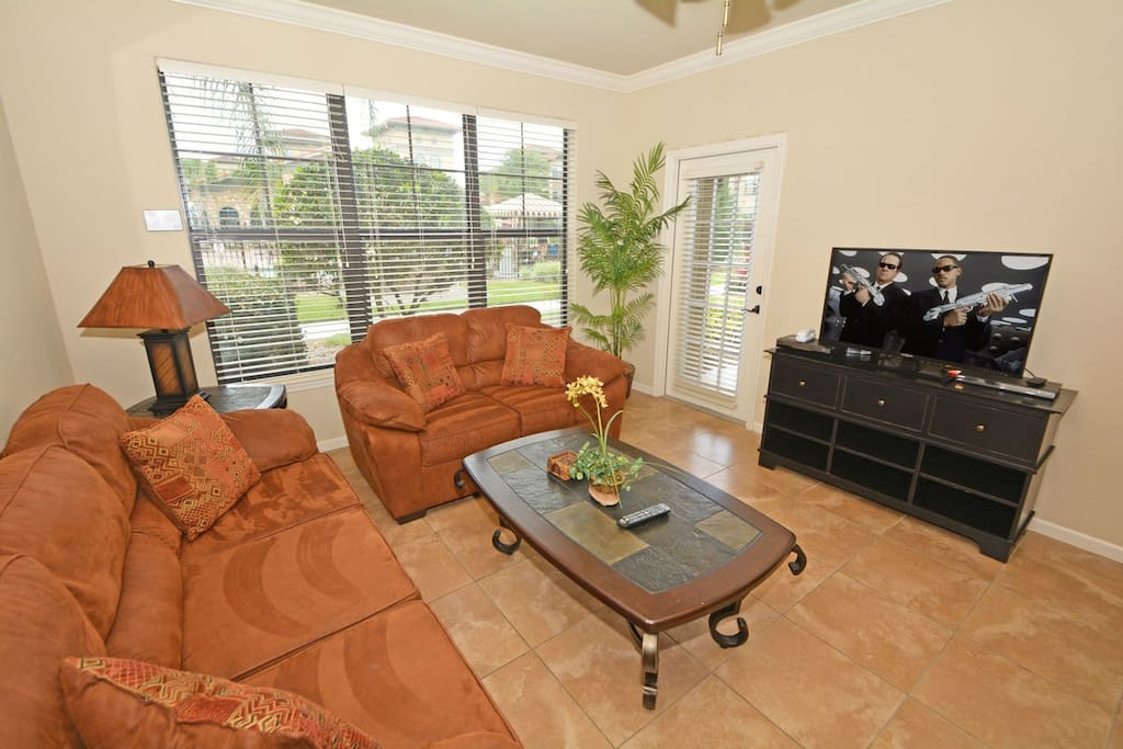 Family seating has 2 sofas, large flatscreen TV, cable TV and door to patio