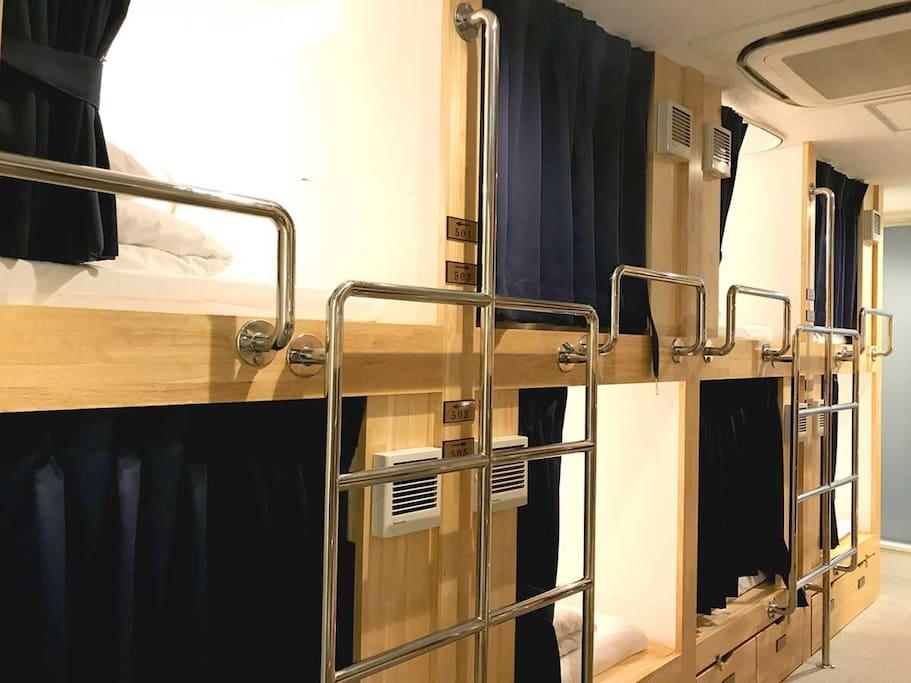 防音性に優れた特注のキャビン風2段ベッド。ブース内の横壁と天井はしっかりとした壁があり、開口部は遮光カーテンで内側まで巻き込める為、閉めると完全なプライベート空間になります。