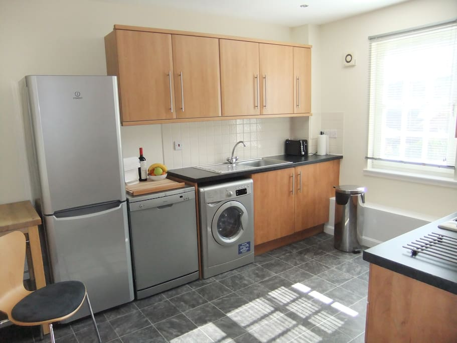 Modern kitchen includes dishwasher, washer and dryer.