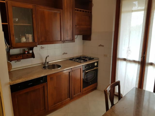 Cucina in legno massello, con porta finestra che da sul balcone dove si trova la lavatrice.