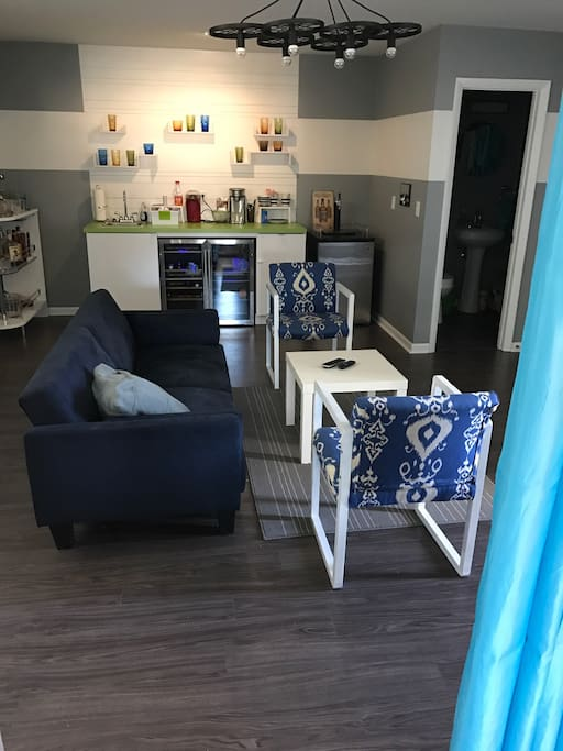 """Living area and bathroom with a keg (help yourself) a fridge and a 42"""" smart tv"""