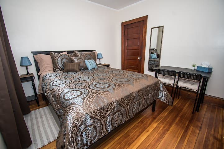 The Black Bedroom - Queen luxury mattress w/ fresh linens. Table w/ 2 chairs. Two lamps. Closet and full length mirror. Blackout curtains & light filtering shades.