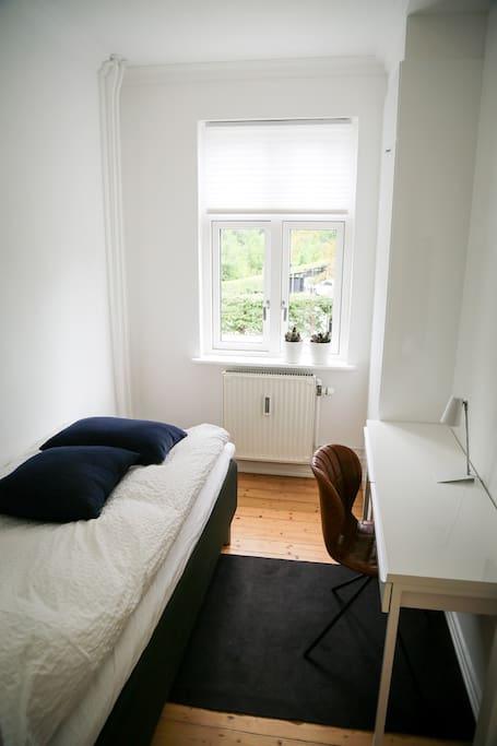 Værelset set fra døren, der går ind til værelset af. Der er udsigt til en skøn ældre park på modsatte side af huset. Sengen er af rigtig god kvalitet med skøn madres, samt dyne og pude med fyld af andedun. Det vil helt sikkert give dig en skøn søvn.
