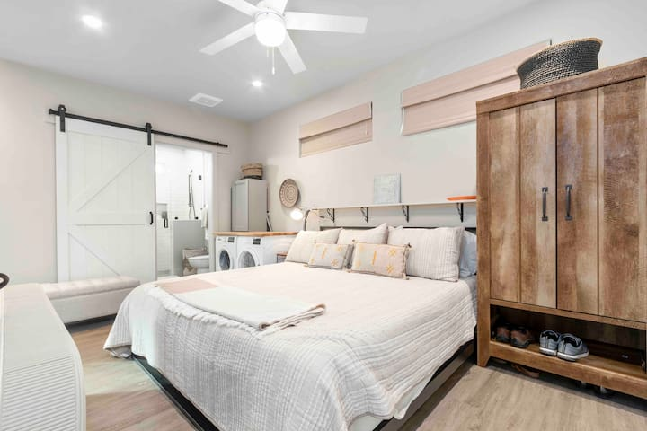 """Luxurious bedroom area with 60"""" TV, ceiling fan and king size bed. This bedroom is partially open to rest of the space."""
