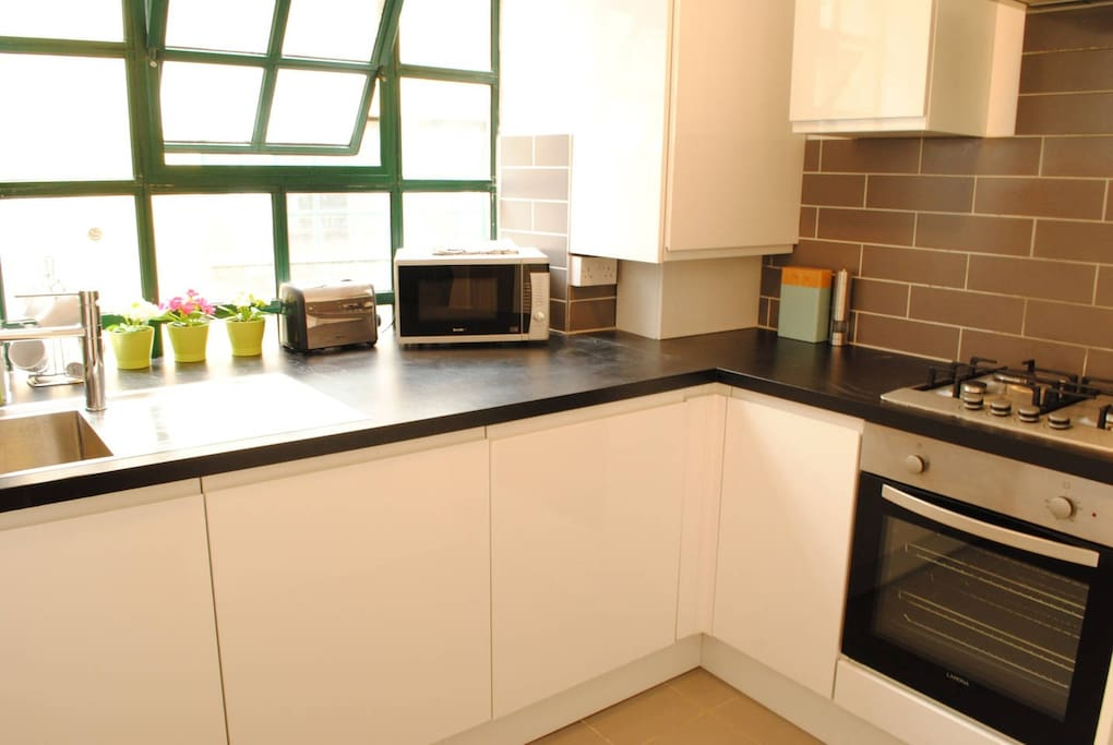 Modern Kitchen with Washer Dryer, Microwave, Toaster, Kettle, Cutlery, Glasses etc