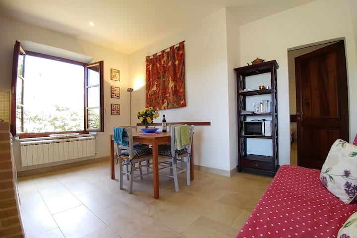 Albegna, living room and kitchen corner with its large window that comes with traditional wooden shutters
