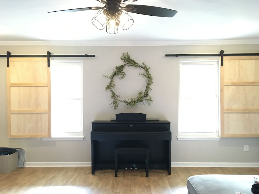 Let as much light in with our custom barn door shutters. Relax and play a tune on our electric Yamaha Piano.