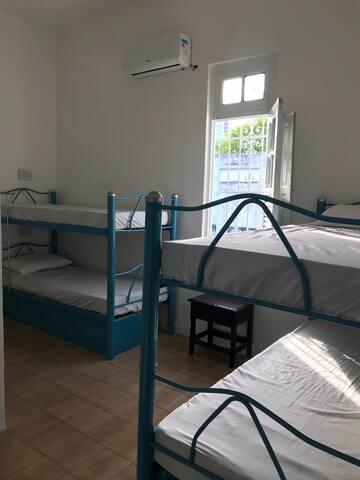 Quarto com dois beliches, banheiro, ar-condicionado e gaveteiros para as roupas