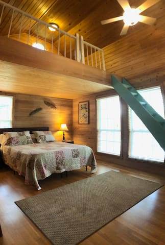 Bedroom features a queen size bed with double windows overlooking the river. There is a loft above.