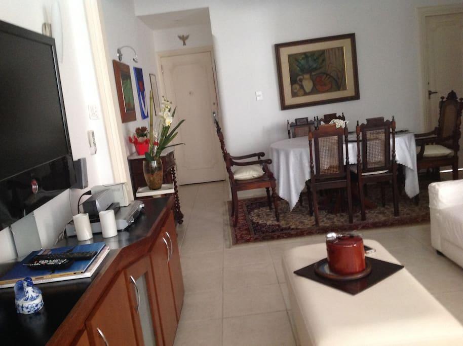 Ampla sala com 3 ambientes: sala de jantar, sala de estar com TV, e estudio.