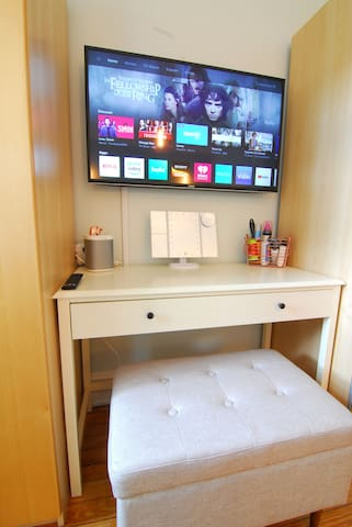 """Vanity area with tufted storage bench, lighted makeup mirror and 43"""" 4K ultra HDTV with casting capability and Netflix."""