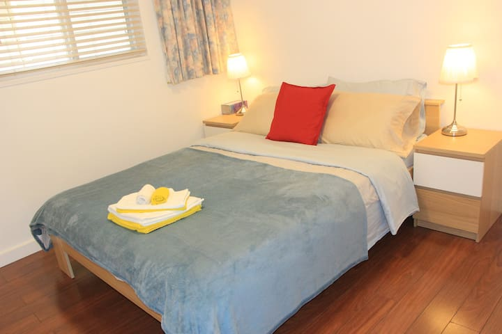 Queen size bed with  medium firm mattress; window with blackout curtain