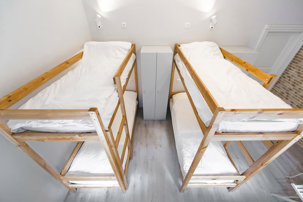 Общий вид комнаты. Две двухъярусных кровати, удобные ящики для хранения личных вещей, зеркало, журнальный столик.