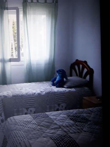 Chambre avec deux lits + un lit en plus situé sous un des lit