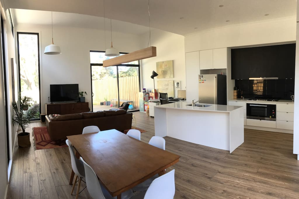 Open plan kitchen, living and dining with access to rear backyard with deck and lawn, and paved courtyard to the west.