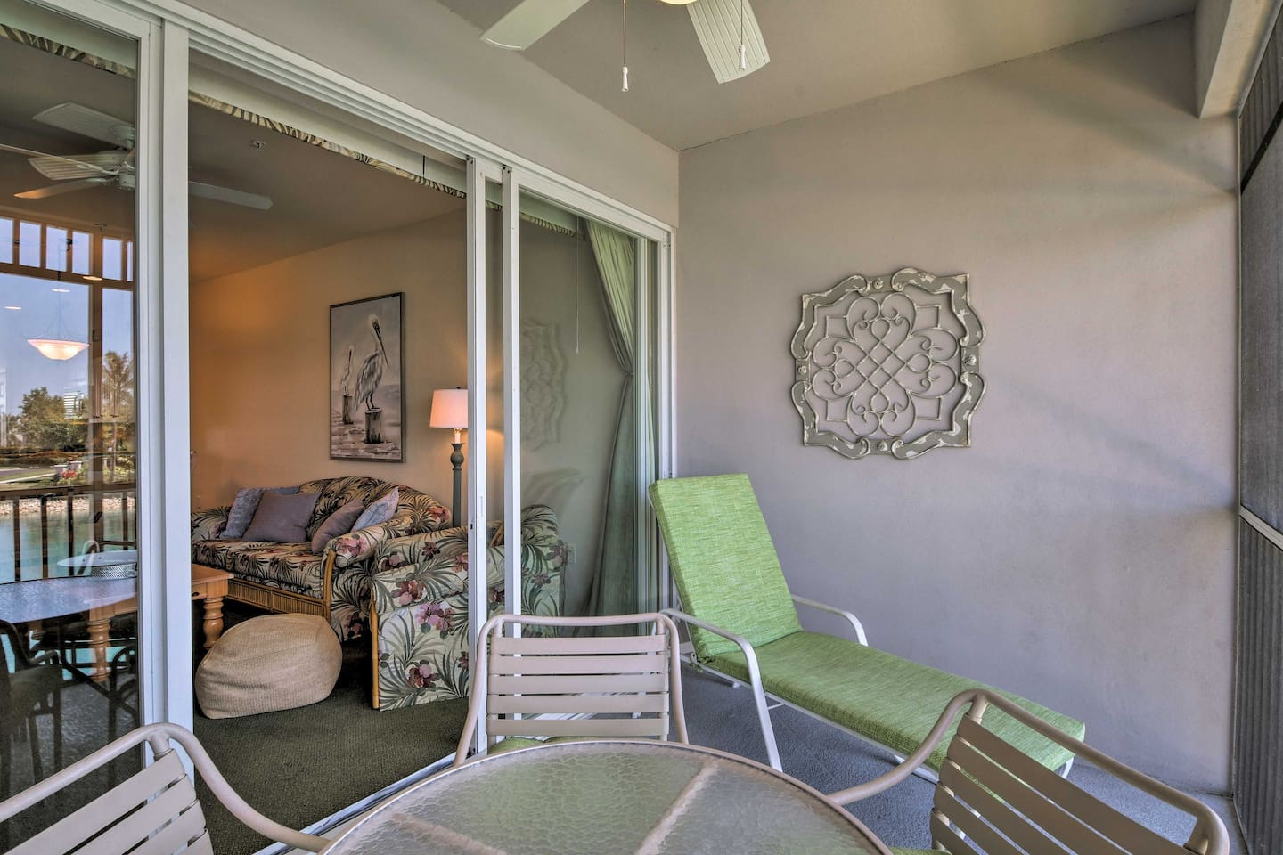 The lanai offers a lounge chair and outdoor dining table.