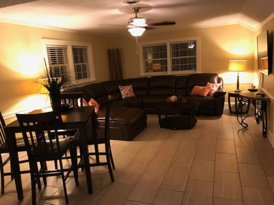 Large living space with leather sectional and breakfast table.